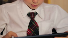 little boy schoolboy 8 years closeup in a white shirt and tie sat at his desk - stock footage
