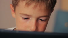 Handsome young boy using  touchscreen tablet technology and reading Stock Footage