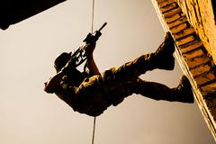 rappeling with weapons - stock photo
