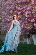 Beautiful pregnant woman in blooming garden - stock photo