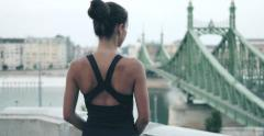 Young sporty girl looking at Budapest next to Liberty Bridge Stock Footage