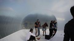 People walk inside plastic bubble art installation in Berlin - stock footage
