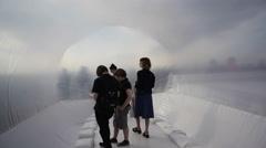 People walk inside plastic bubble art installation refugee raft boat, Berlin - stock footage