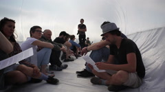 People sit inside plastic bubble refugee raft boat art installation, Berlin - stock footage