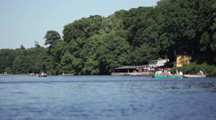 Boat house at the lake, people on boats on a sunny summer day Stock Footage