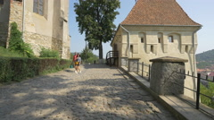 Walking on an alley between Monastery Church and Blacksmiths Tower, Sighisoara Stock Footage