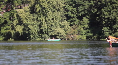 3 teenagers row boat at the lake on a sunny summer day, Berlin Stock Footage