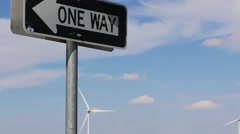One Way Road Sign with Wind Turbine Blades in Background Stock Footage