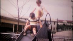 2511 - children play on the slide at school playground - vintage film home movie Stock Footage