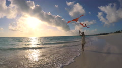 Asian Chinese girl with red kite enjoying tropical sunset beach Stock Footage