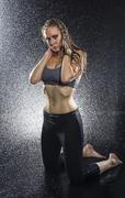 Athletic Woman Kneeling in Studio with Water Spray Stock Photos
