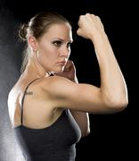 Sporty Woman in Combat Pose Against Black Stock Photos