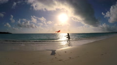 Asian Chinese girl at sunset playing with red kite on beach Stock Footage