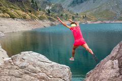 Girl athlete jumps between its stones in the mountains - stock photo