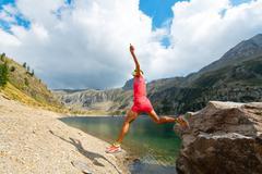 .Woman jumps from a rock near a mountain lake Stock Photos