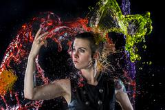 Modern Woman Being Splashed with Colorful Water - stock photo