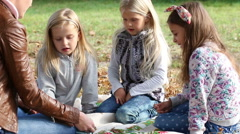 Young woman at work as educator reading book to girls in park Stock Footage