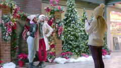 Teen Takes Photos Of Friends In Front Of Festive Christmas Decor Stock Footage
