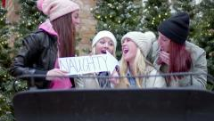 Teens Sit In Santa's Sleigh At Mall, Girl Points Naughty Sign At Friend As Joke Stock Footage