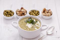 A delicious pea cream with aromatic spices on a wooden table. Stock Photos