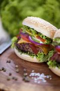 Beef burgers on a wooden board with aromatic spices - stock photo
