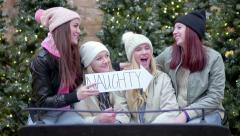 Group Of Fun Teens Sit In Santa's Sleigh, Hold Up Naughty And Nice Signs Stock Footage