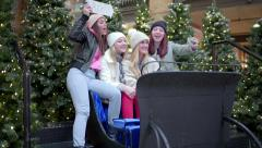 Group Of Fun Girls Take Photos Together In Santa's Sleigh At Mall Stock Footage