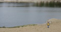 Little Girl Child in Yellow Clothes is Standing at The River Lake Granddaughter Stock Footage