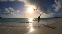 Young Asian Chinese girl in silhouette playing with kite on beach Stock Footage