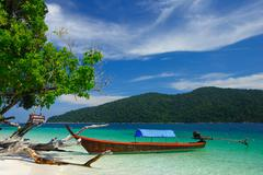 Longtail boat on the beach of Rawi island, Thailand - stock photo