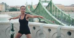 Young pretty female dancer practising next to Liberty Bridge, Budapest - stock footage