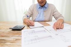 Stock Photo of senior woman with papers and calculator at home