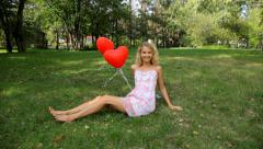 happy girl with red heart balloons on green grass - stock footage