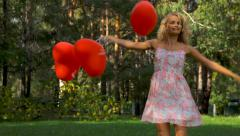 happy girl having fun with heart balloons outdoors - stock footage