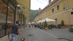 A man with a kart and a garbage man walking on Apollonia Hirscher street, Brasov Stock Footage
