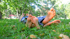 Barefoot feet of two kids on green grass Stock Footage