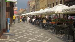 Tourists walking on Republicii street, near Publick restaurant, Brasov Stock Footage
