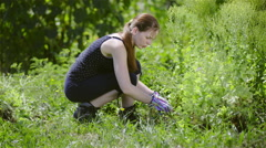 Stock Video Footage of Woman cutting out weeds from garden 4K