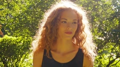 Young happy pretty girl walking in sunny park, smiling, slow motion, backlight. Stock Footage