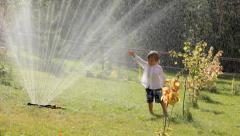 cute little boy standing under sprinkler water - stock footage