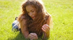 Stock Video Footage of 4K Happy caucasian girl have fun in park laying on grass.