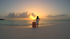 African American girl with suitcase on beach at sunrise Stock Footage