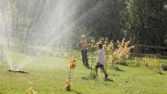happy children having fun with sprinkler - stock footage