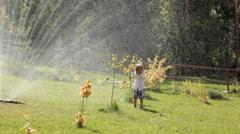 little child boy standing under sprinkler water - stock footage