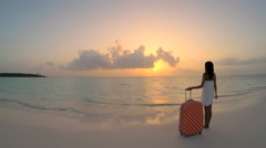 Young African American girl with suitcase on tropical sunset beach Arkistovideo