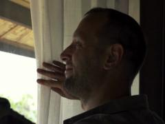 Happy man unveil curtain and looking through the window NTSC - stock footage