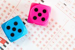 Lotto ticket and dice - stock photo