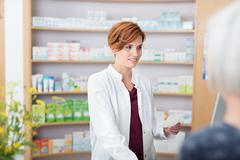 Young pharmacist assisting on older woman - stock photo