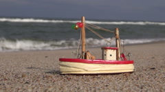 Wooden ship model  toy by the sea on beach sand Stock Footage