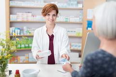 Woman patient paying for her medication - stock photo